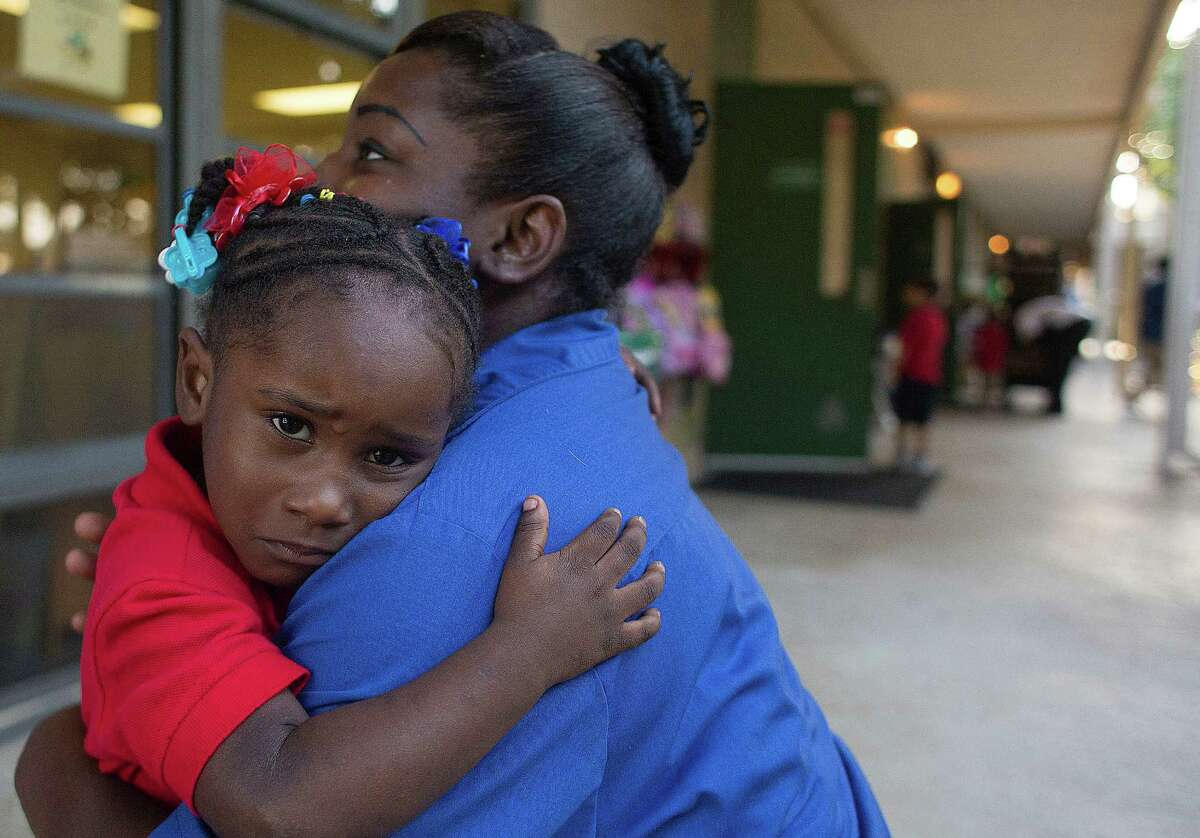 T'Ieviea Smith, 3, gets one last hug from her mom, LaTonya Smith, as she begins her first day at Garden Oaks Elementary School.