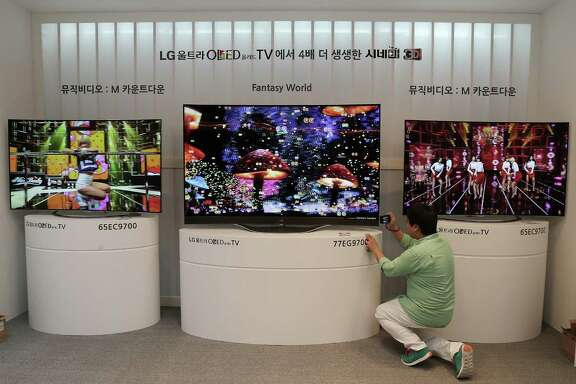 A journalist takes pictures of an LG Electronics' Ultra organic light-emitting diode 3-D TV during a press unveiling on Monday in Seoul, South Korea.