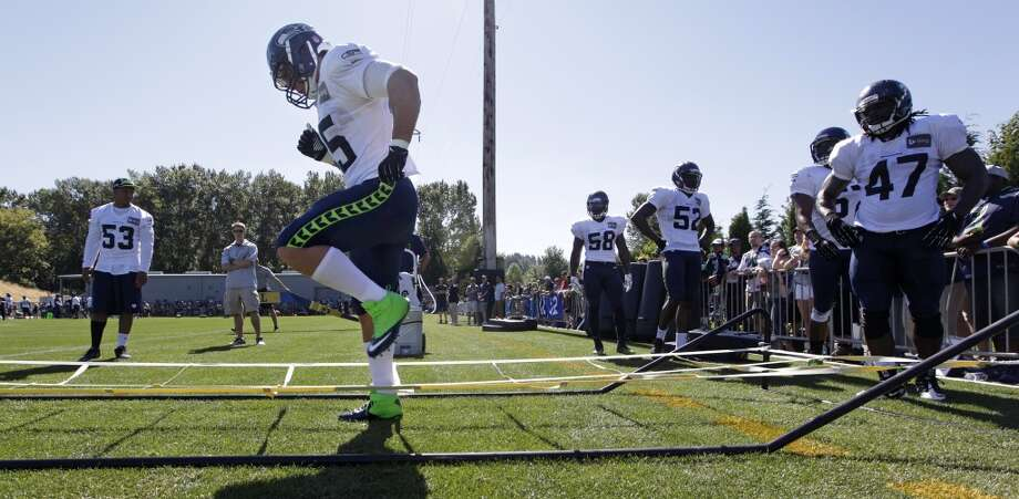 The Seattle Seahawks' Brock Coyle runs through an obstacle as other linebackers wait their turn behind him at practice during Seahawks training camp on Wednesday, July 30. Photo: Elaine Thompson, Associated Press
