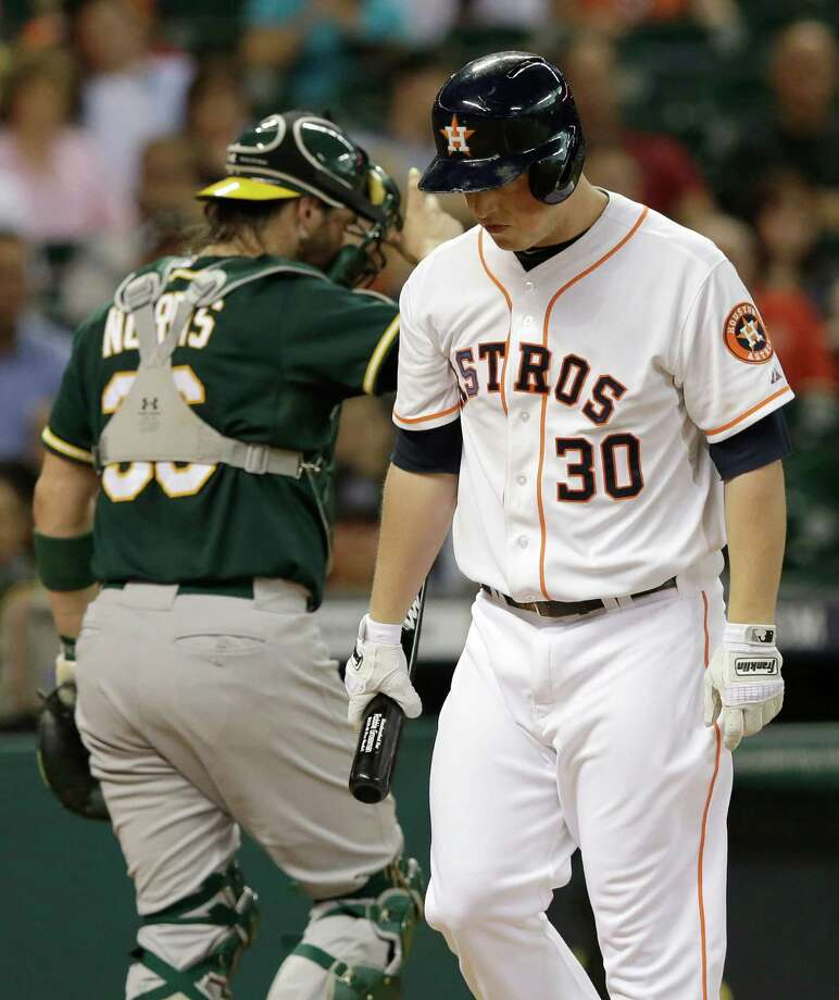 Houston Astros' Matt Dominguez (30) walks off after striking out against the Oakland Athletics to end the second inning of a baseball game Monday, Aug. 25, 2014, in Houston. Oakland Athletics catcher Derek Norris, left, heads to the dugout. (AP Photo/Pat Sullivan) Photo: Pat Sullivan, Associated Press / AP