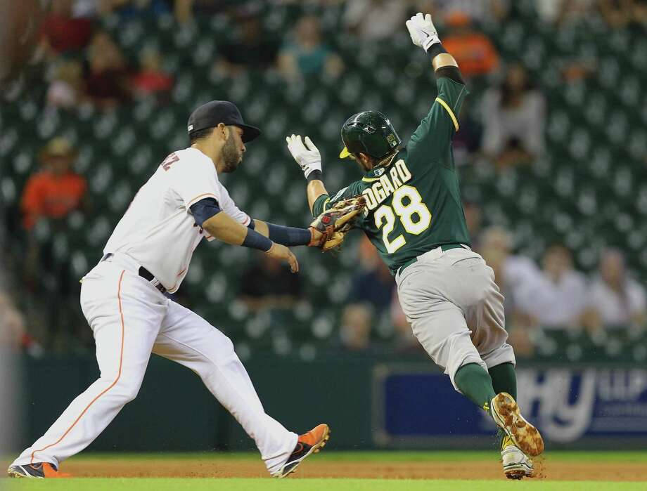Try as he might, Oakland's Eric Sogard can't escape the tag of Astros shortstop Marwin Gonzalez in Monday night's game at Minute Maid Park. Photo: Bob Levey, Stringer / 2014 Getty Images