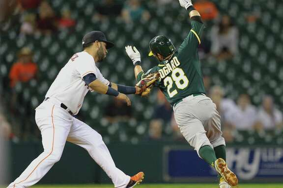 Try as he might, Oakland's Eric Sogard can't escape the tag of Astros shortstop Marwin Gonzalez in Monday night's game at Minute Maid Park.