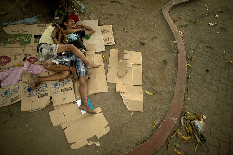 TOPSHOTS Homeless people sleep on the ground at a park in Manila on August 24, 2014. The Philippines announced in April plans to spend more on infrastructure and introduce other reforms to try to lift millions out of poverty. The revised Philippine Development Plan sets more ambitious economic targets to address persistent concerns that poor Filipinos are not enjoying the benefits of the country's recent dramatic economic growth. AFP PHOTO /NOEL CELISNOEL CELIS/AFP/Getty Images Photo: Noel Celis, AFP/Getty Images