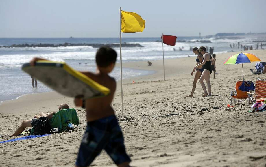 One beach has a yellow flag signaling beachgoers to use caution for possible rip currents and a nearby beach has a no swimming allowed red flag along the ocean Monday, Aug. 25, 2014, in Spring Lake, N.J. (AP Photo/Mel Evans) Photo: Mel Evans, Associated Press