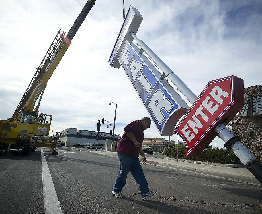 Ken Wells of Sign Co Pro guides the repaired San Bernardino County Fair sign back into its original place on Seventh Street in Victorville, Calif., Monday, Aug. 25, 2014. The historic sign was damaged in a wind storm last winter (AP Photo/Daily Press, James Quigg) Photo: James Quigg, Associated Press