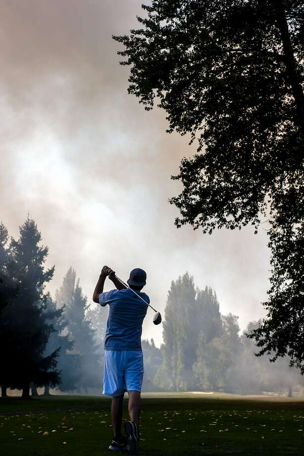 "Smoke from a field fire adjacent to Riverside Golf Club billows onto the 12th hole as Johnie Williams, 21, of Olympia, Wash., tees off on Monday, Aug. 25, 2014 in Chehalis, Wash. According to Chehalis Fire Chief Rob Gebhart, the field was surrounded by dirt, so the fire ""wasn't going anywhere,"" Gebhart said. As of late Monday afternoon the fire was contained and the golf course was free of smoke. (AP Photo/The Chronicle, Pete Caster) Photo: Pete Caster, Associated Press"