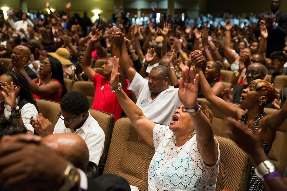 People raise their arms during the funeral service for Michael Brown at Friendly Temple Missionary Baptist Church in St. Louis, Monday, Aug. 25, 2014. Hundreds of people gathered to say goodbye to Michael Brown, the 18-year-old shot and killed Aug. 9 in a confrontation with a police officer that fueled almost two weeks of street protests. (AP Photo/New York Times, Richard Perry, Pool) Photo: Richard Perry, Associated Press