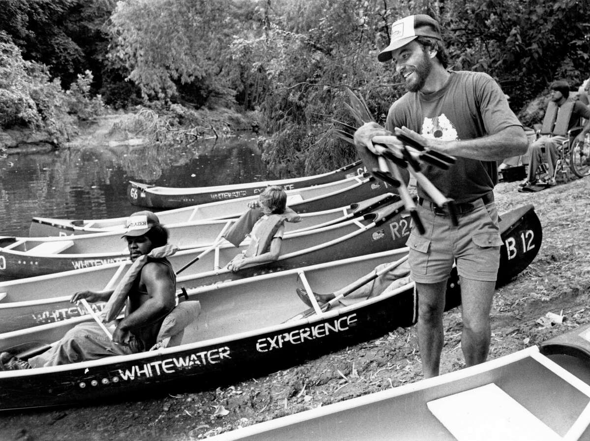 Don Greene in 1980, helping a group of wheelchair-bound people prepare for a canoe trip down Buffalo Bayou. (Chronicle file photo.)