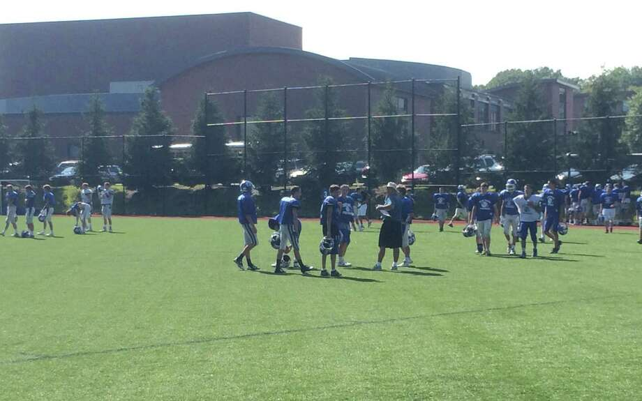 The Darien football team practices on the Darien High School turf baseball field following the first day of the 2014-15 school year on Monday, Aug. 25. Photo: Andrew Callahan / Darien News