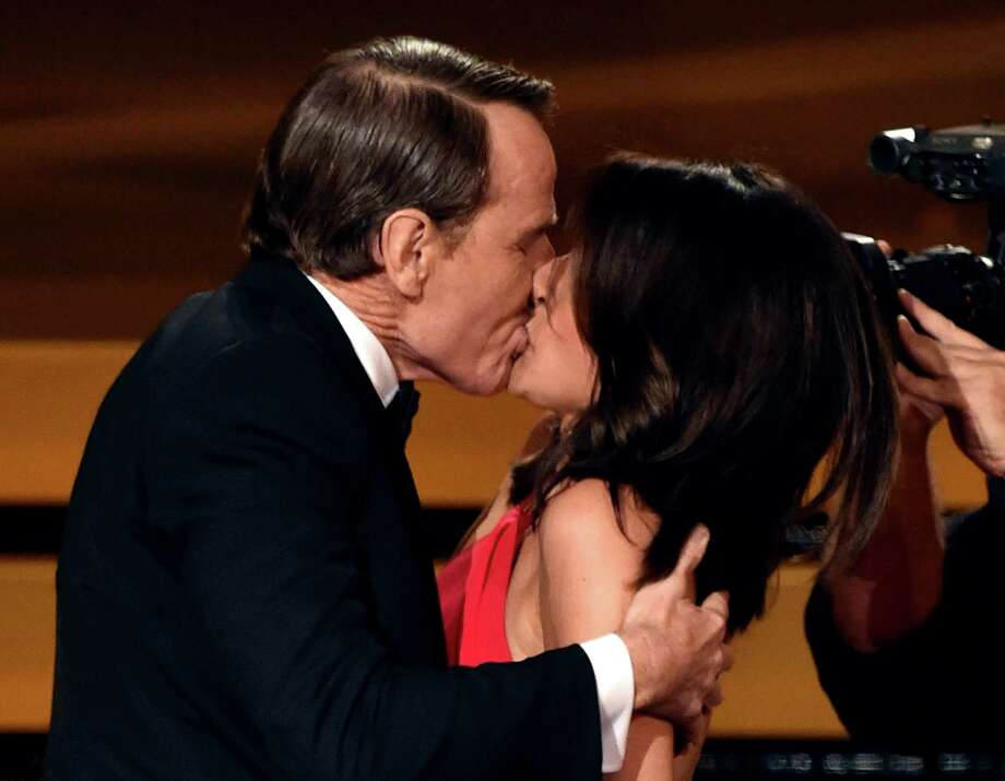 Julia Louis-Dreyfus gets a kiss from Bryan Cranston after she won outstanding lead actress in a comedy series.  Photo: Kevin Winter, Getty Images / JAKLE EMMY