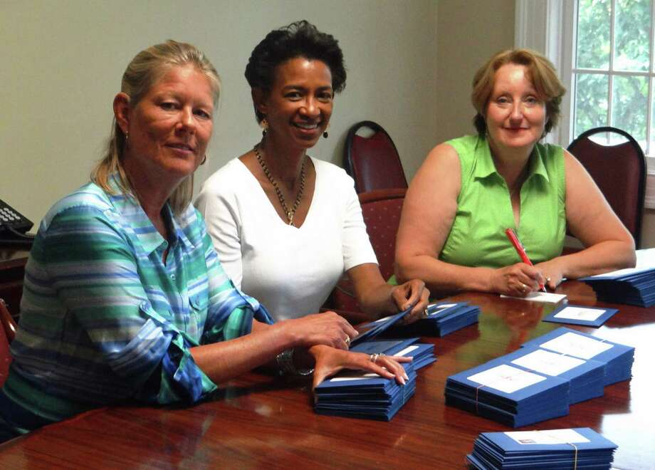 Person-to-Person is hosting its Blues & BBQ benefit on Saturday, Sept. 13. Above, committee members Leslie Hueglin, Taylor McCall-Mazza and Alison de Lavis assemble, address and personalize Blues & BBQ invitations. Photo: Contributed Photo, Contributed / Darien News Contributed