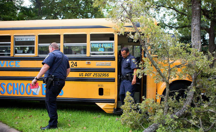 Police investigate the scene of a wreck in the 9500 block of  Briar Forest near Tanglewilde,Tuesday, Aug. 26, 2014, in Houston. Authorities transported 19 students and the driver to the local hospital. Officials said the driver apparently lost control of the bus, which is privately owned, and slammed into a tree. Photo: Cody Duty, Houston Chronicle / © 2014 Houston Chronicle