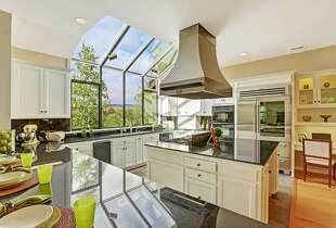 A wall of glass in the kitchen welcomes natural light into the workspace.
