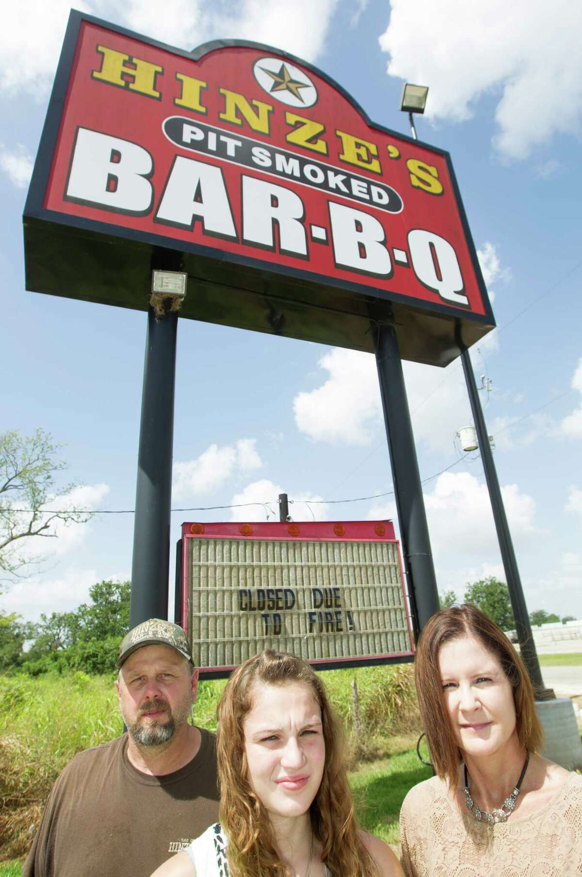 Michael Hinze his daughter Libby, 17, and wife Terry pose for a portrait at their Bar-B-Que restaurant on Friday, Aug. 22, 2014, in Wharton. ( J. Patric Schneider / For the Chronicle )
