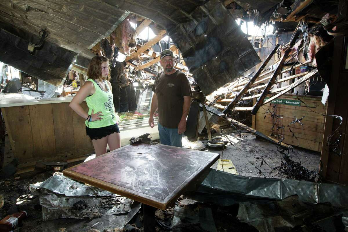 Michael Hinze and his daughter Libby, 17, survey the damage at his Bar-B-Que restaurant on Friday, Aug. 22, 2014, in Wharton. ( J. Patric Schneider / For the Chronicle )