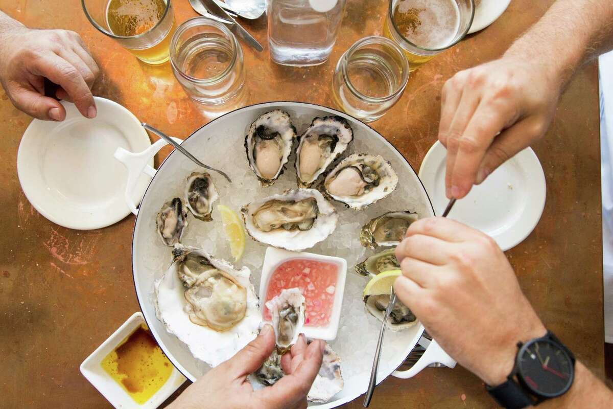 Diners enjoy oysters at the small neighborhood restaurant Red Hill Station in San Francisco.