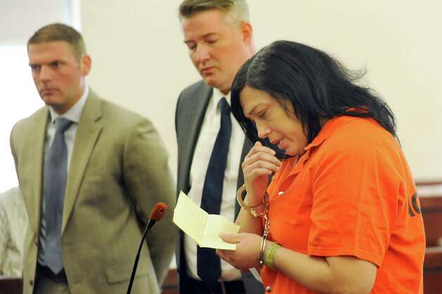 Suzette Guzman-Moore, right, reads a statement during her sentencing on Tuesday, Aug. 26, 2014, at the Albany County Judicial Center in Albany, N.Y. Joining her are public defender Joe Meany, center, and assistant district attorney Daniel Lynch. Guzman-Moore, who was a licensed practical nurse at Albany Medical Center, was convicted of stealing the identities of dozens of hospital patients to score credit cards. (Cindy Schultz / Times Union) Photo: Cindy Schultz / 00028313A