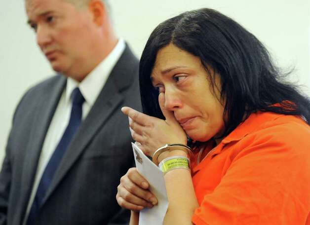 Suzette Guzman-Moore, right, shows emotion after reading a statement during her sentencing on Tuesday, Aug. 26, 2014, at the Albany County Judicial Center in Albany, N.Y. Public defender Joe Meany joins her. Guzman-Moore, who was a licensed practical nurse at Albany Medical Center, was convicted of stealing the identities of dozens of hospital patients to score credit cards. (Cindy Schultz / Times Union) Photo: Cindy Schultz / 00028313A