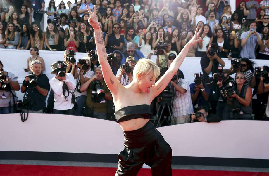 Miley Cyrus, arriving at Sunday's MTV Video Music Awards, urges fans to donate to homeless youth. Photo: Matt Sayles, Associated Press