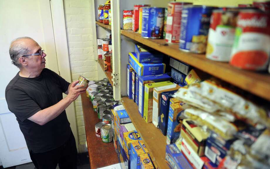 Volunteer John Nieves, of Danbury, stocks the shelves at the food pantry at Jericho Partnership Tuesday, Aug. 26, 2014 at their location behind St. Paul's Lutheran Church in Danbury, Conn. The pantry is part of The Danbury Food Collaborative (DFC), which is comprised of twelve non-profit agencies, which just received a $25,000 grant to provide food to Danbury residents. Photo: Autumn Driscoll / Connecticut Post