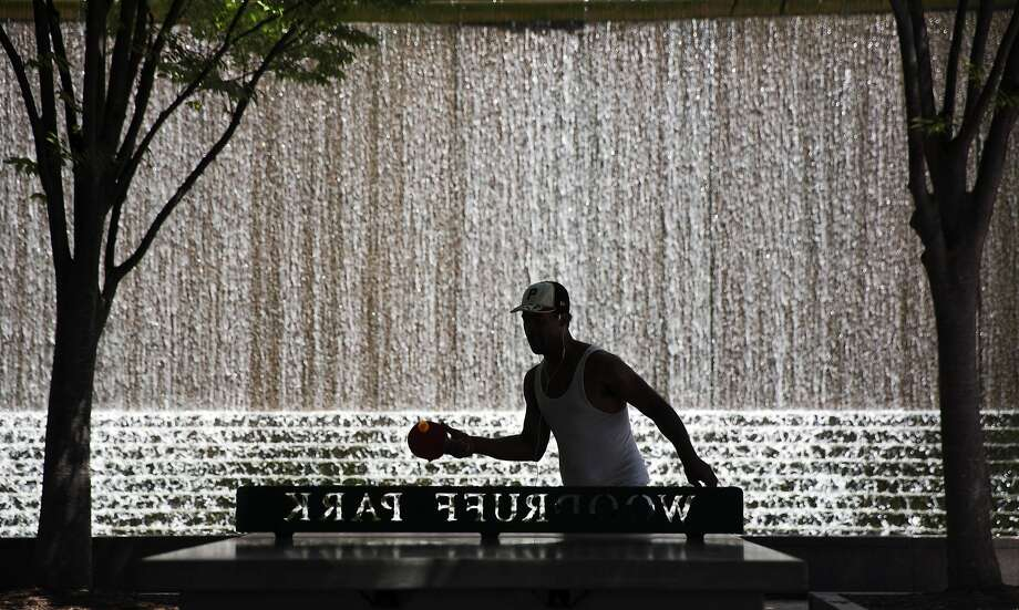 Pong al fresco:Leonard Crewe plays table tennis in front of a large fountain in Woodruff Park, Atlanta. Photo: David Goldman, Associated Press