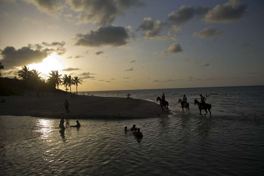 Seaside equestrians ride along Mi Cayito beach on the outskirts of Havana. Photo: Ramon Espinosa, Associated Press