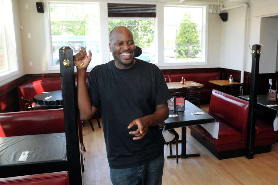 Owner Paul Osakwe stands in the dining room at Zeke's Bar and Grill, which opened recently on Barnum Ave., in Bridgeport, Conn. Aug. 26, 2014. Photo: Ned Gerard / Connecticut Post
