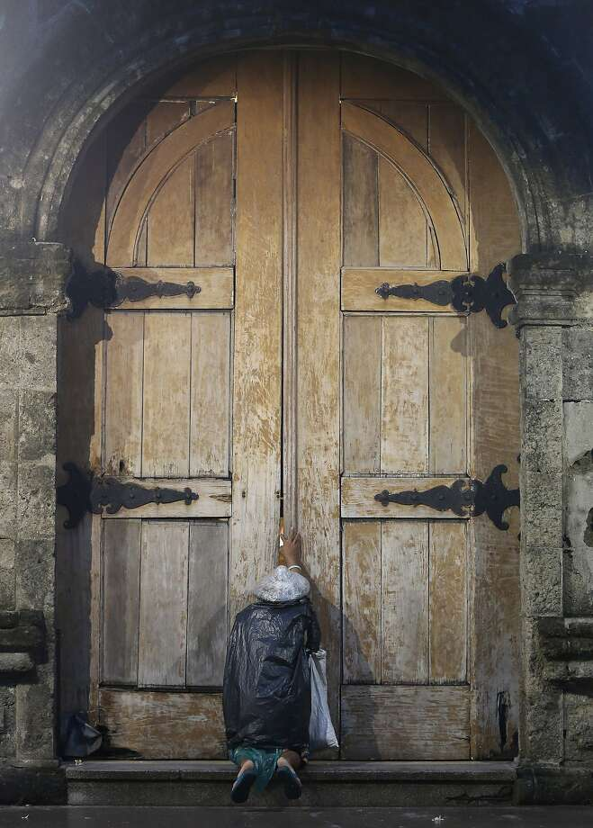 A Filipino woman wearing plastic sheets to protect herself from the rain kneels down and touches the doors of a church while praying in Manila, Philippines, Tuesday, Aug. 26, 2014. (AP Photo/Aaron Favila) Photo: Aaron Favila, Associated Press
