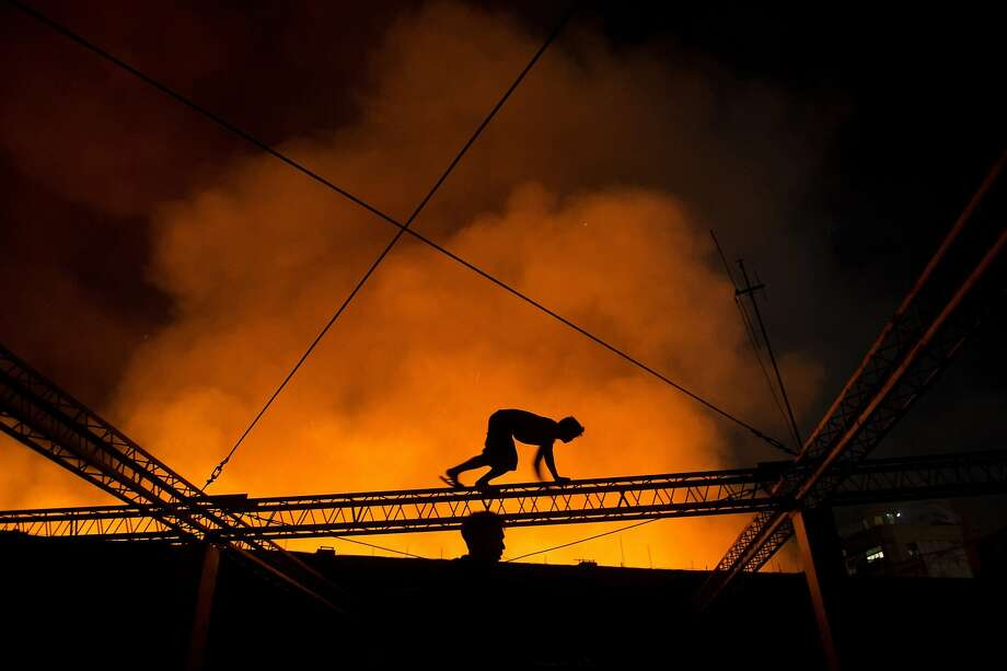 Highly motivated rubbernecker:A man crawls on a truss of a building to get a better view of a fire engulfing a warehouse in Manila. Photo: Noel Celis, AFP/Getty Images