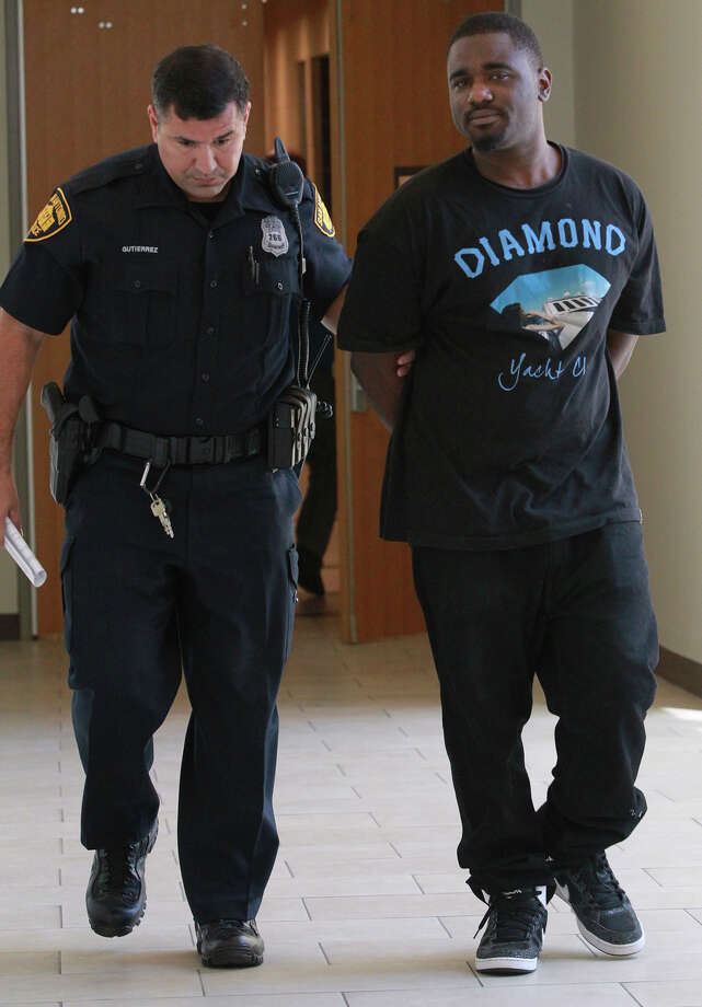 Murder suspect Namon Jefferson (right) is escorted to a police car Tuesday August 26, 2014. Jefferson is suspected of a murder that took place in a grocery store parking lot during a drug deal gone bad according to San Antonio police officer Douglas Greene. Photo: JOHN DAVENPORT, San Antonio Express-News / ©San Antonio Express-News/John Davenport