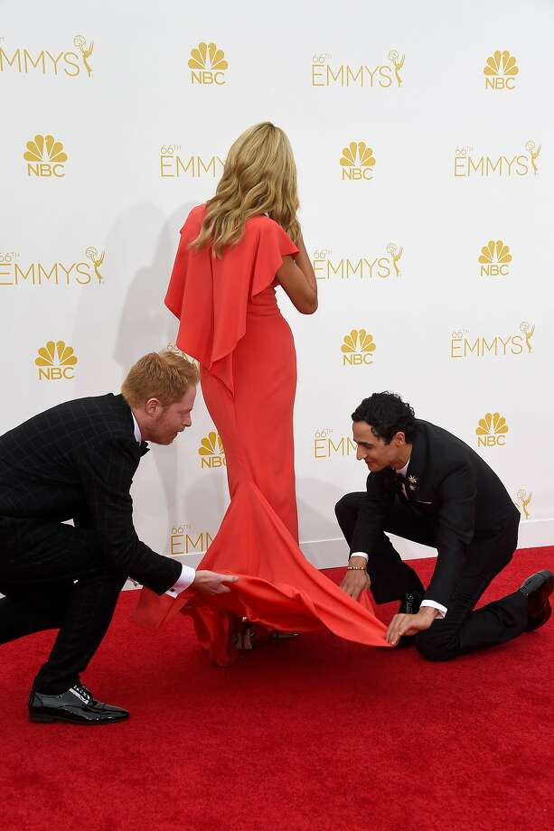 """Your train is tangled, m'lady. Allow us:The chivalrous Jesse Tyler Ferguson (""""Modern Family"""") and designer Zac Posen attend to Heidi Klum's gown at the Emmy Awards in Los Angeles. Photo: Frazer Harrison, Getty Images"""