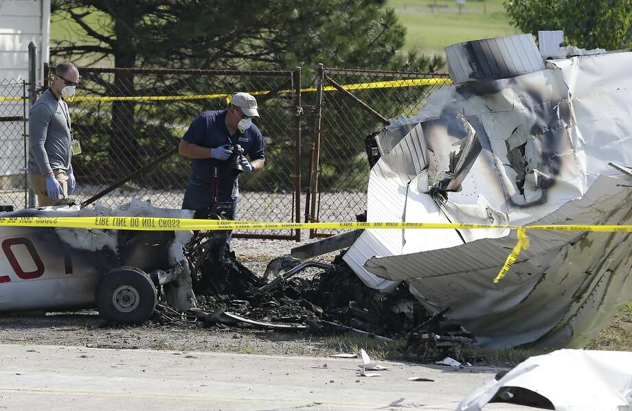 Investigators look over the wreckage of a plane that crashed as it rests on the side of a road Tuesday, Aug. 26, 2014, in Richmond Heights, Ohio. The Cessna 172R crashed and burst into flames just after takeoff from a regional airport outside of Cleveland on Monday, killing all four people on board, according to the Ohio State Highway Patrol. (AP Photo/Tony Dejak) Photo: Tony Dejak, Associated Press