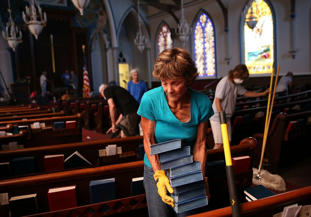 NAPA, CA - AUGUST 26: Jane Young moves a stack of bibles as she helps clean up the earthquake-damaged First Presbyterian Church on August 26, 2014 in Napa, California. Two days after a 6.0 earthquake rocked the Napa Valley, residents and wineries are continuing clean up operations. (Photo by Justin Sullivan/Getty Images)