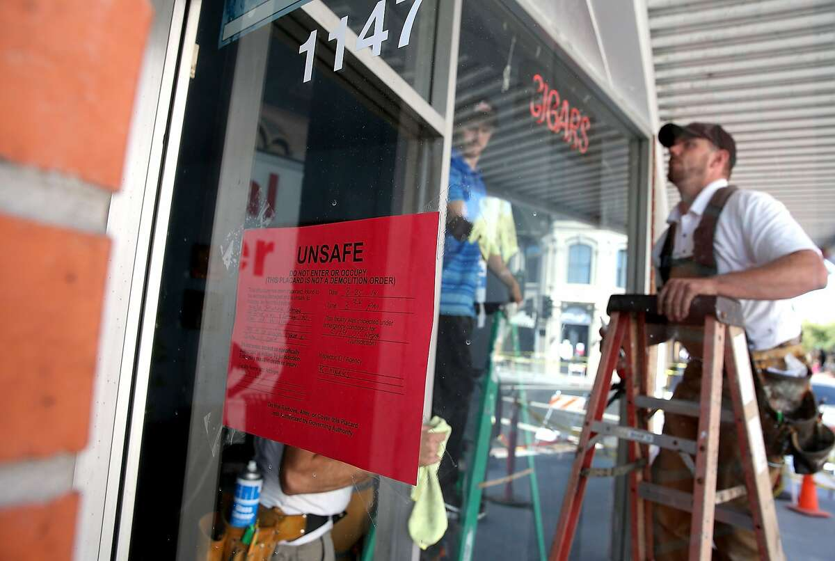 Workers replace a broken window at a red tagged building that sustained earthquake damage on August 26, 2014 in Napa, California. Two days after a 6.0 earthquake rocked the Napa Valley, residents and wineries are continuing clean up operations.