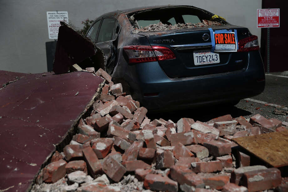 NAPA, CA - AUGUST 26:  A for sale sign is posted on the back of an earthquake-damaged car on August 26, 2014 in Napa, California.  Two days after a 6.0 earthquake rocked the Napa Valley, residents and wineries are continuing clean up operations.  (Photo by Justin Sullivan/Getty Images) Photo: Justin Sullivan, Staff / Getty Images / 2014 Getty Images