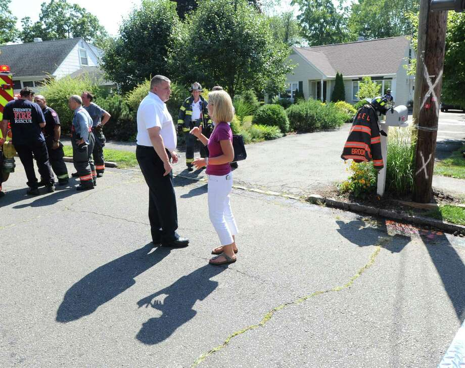 Greenwich Fire Chief, Peter Siecienski, left, at the scene of the aftermath of a house fire at 14 Bonwit Rd. in the Riverside section of Greenwich, Conn., Tuesday afternoon, Aug. 26, 2014. According to Greenwich fire officials on the scene, the small fire inside the house was extinguished by the department quickly and there were no injuries. Photo: Bob Luckey / Greenwich Time