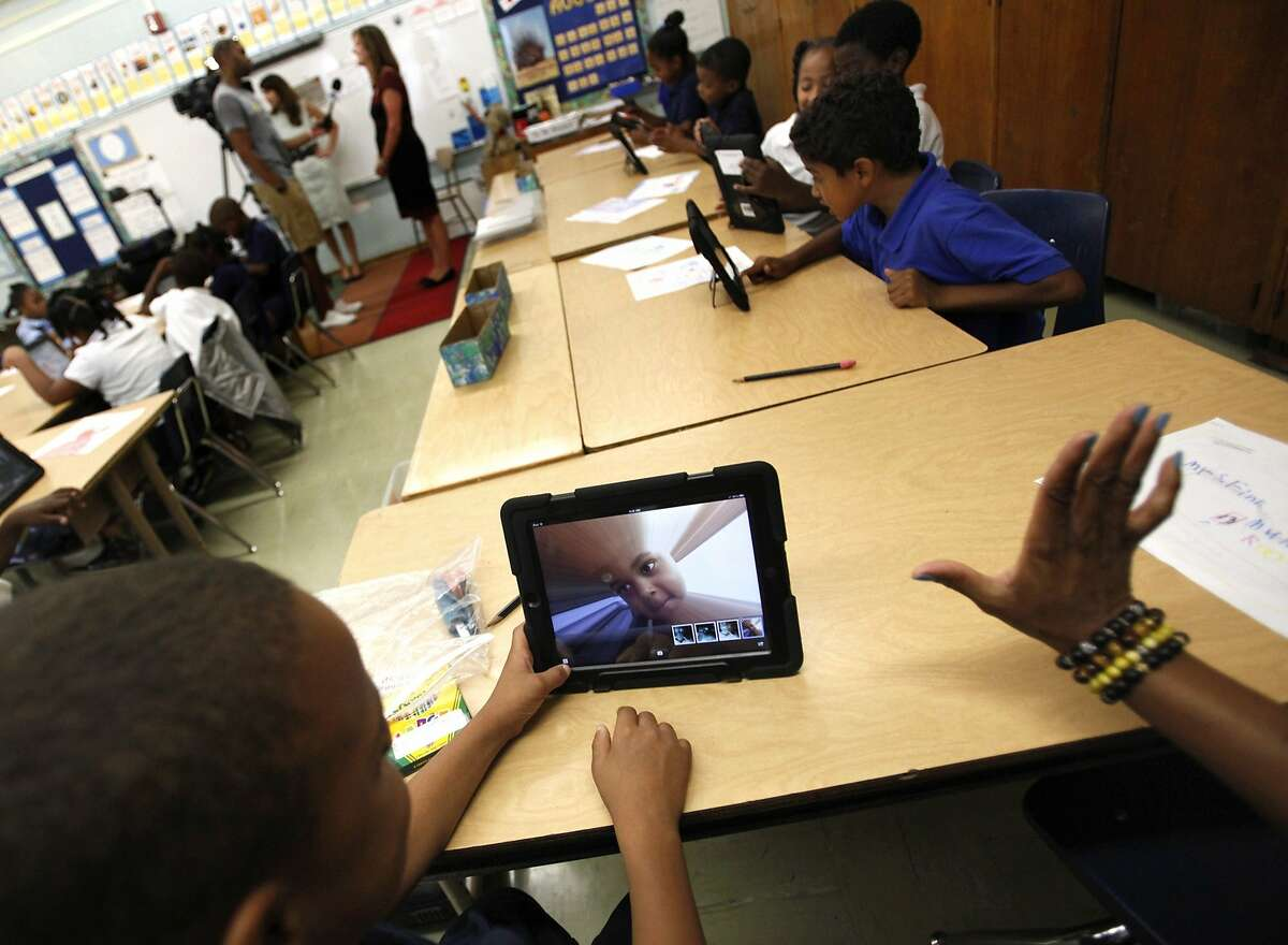 FILE - In this Aug. 27, 2013, file photo, Muhammad Nassar Jr. takes a picture of himself using an i-pad during Karen Finkel's class at Broadcrest Elementary School in Carson, Calif. Faced with criticism about the planning and rollout of a $1 billion effort by the Los Angeles Unified School District to provide iPads to all students, Superintendent John Deasy has suspended future use of a contract with Apple Inc. (AP Photo/Los Angeles Times, Bob Chamberlin, File) NO FORNS; NO SALES; MAGS OUT; ORANGE COUNTY REGISTER OUT; LOS ANGELES DAILY NEWS OUT; INLAND VALLEY DAILY BULLETIN OUT; MANDATORY CREDIT, TV OUT