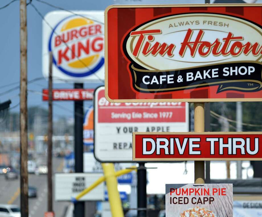 Signs for Tim Hortons and Burger King beckon drivers in Erie, Pa. The burger chain is buying the Canadian doughnut shops. Photo: Christopher Millette, Associated Press
