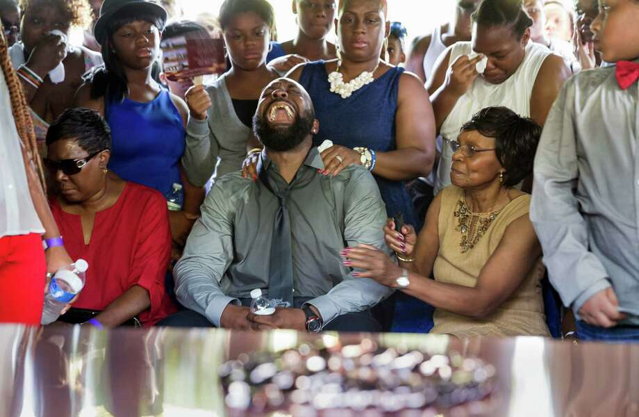 Michael Brown Sr., yells out as his son, Michael Brown Jr.'s casket is lowered into the ground at St. Peter's Cemetery in St. Louis, on Monday. Thousands attended the funeral of the 18-year-old killed by a policeman Aug. 9 in Ferguson, Missouri. Photo: Richard Perry / AFP / Getty Images / AFP