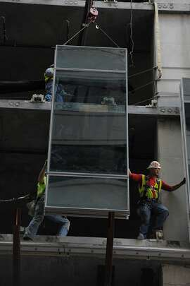 Construction workers install window panels on 350 mission on August 26, 2014 in San Francisco, CA. The building will have a very unusual undulating glass skin with each panel tipping in or out by 7 inches.
