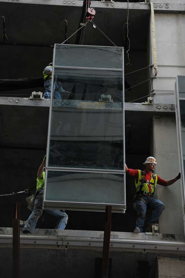 Construction workers install window panels for the rising 30-story tower at 350 Mission St. in S.F. Photo: Craig Hudson, The Chronicle