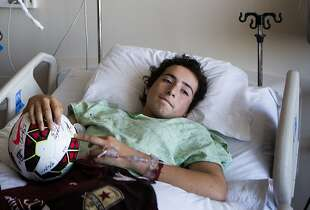 Thirteen-year-old Nicholas Dillon lies in his hospital bed after being visited by Sacramento Republic FC player, and Napa native, Max Alvarez at UC Davis Medical Center in Sacramento, California, August 26, 2014.  Dillon's pelvis was crushed by a falling chimney at his Napa home during Sunday's 6.0 magnitude earthquake.