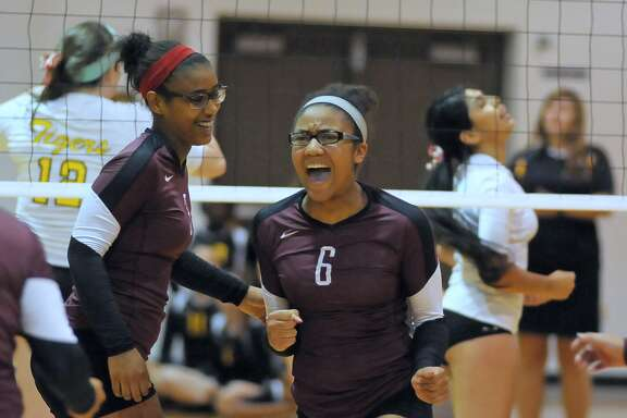 Kamryn Linton (3) and Jazmyne Pickney (6) celebrate a point for Reagan during their game with Spring Woods earlier this month.