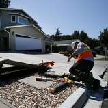 On Twin Oaks Drive in Napa, Calif. a utility worker makes repairs near a red tagged home the RMS group is investigating Tuesday August 26, 2014. Risk Management Solutions (RMS) is a group of professionals that look at structural damage, liquefaction zones and interviews to determine the cost of the damage from an earthquake like the South Napa event.