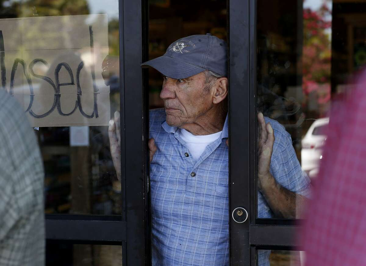 Browns Valley Market owner Larry Giovannoni looks out from his market which was badly damaged in the earthquake as he answers questions from the RMS team Tuesday August 26, 2014 in Napa, Calif. Risk Management Solutions (RMS) is a group of professionals that look at structural damage, liquefaction zones and interviews to determine the cost of the damage from an earthquake like the South Napa event.