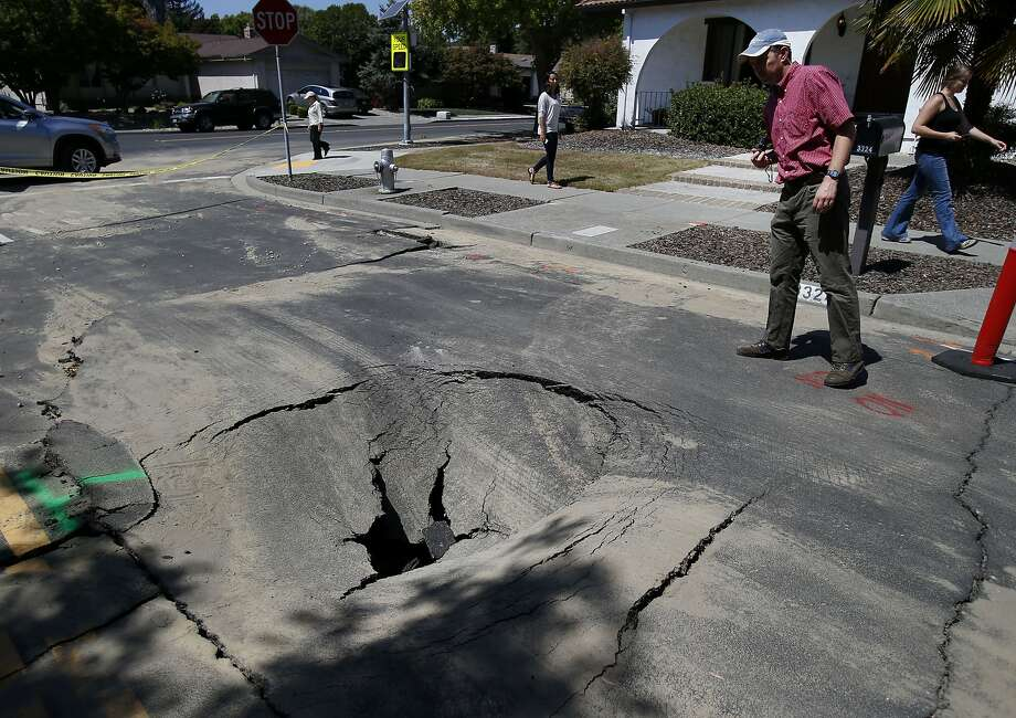 Engineer Justin Moresco (right) of RMS looks over a hole created by the earthquake in Napa, Calif. Risk Management Solutions (RMS) is a group of professionals that look at structural damage, liquefaction zones and interviews to determine the cost of the damage from an earthquake like the South Napa event. Photo: Brant Ward, San Francisco Chronicle