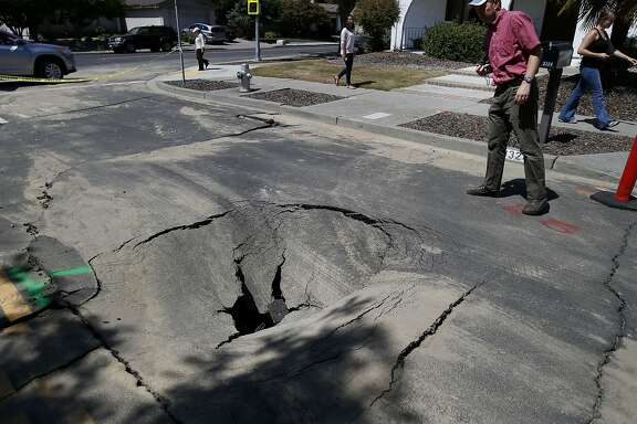 Engineer Justin Moresco (right) of RMS looks over a hole created by the earthquake in Napa, Calif. Risk Management Solutions (RMS) is a group of professionals that look at structural damage, liquefaction zones and interviews to determine the cost of the damage from an earthquake like the South Napa event.