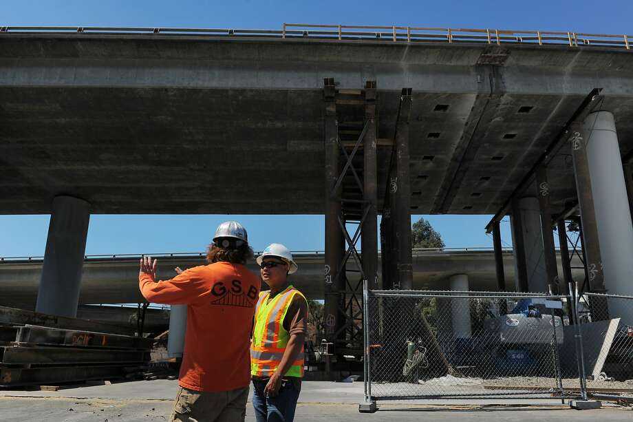 Resident engineer Andrew Yan (right) confers with a contractor beneath Interstate 280 just west of Indiana Street. Photo: Craig Hudson, The Chronicle