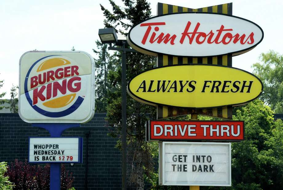 A Burger King sign and a Tim Hortons sign are displayed on St. Laurent Boulevard in Ottawa, Canada, on Monday, Aug. 25, 2014. Canada's iconic coffee chain, Tim Hortons, and Miami-based Burger King say they will join forces, but will operate as independent brands to form the world's third-largest quick service restaurant company. (AP Photo/The Canadian Press, Sean Kilpatrick) ORG XMIT: CPT101 Photo: Sean Kilpatrick / The Canadian Press