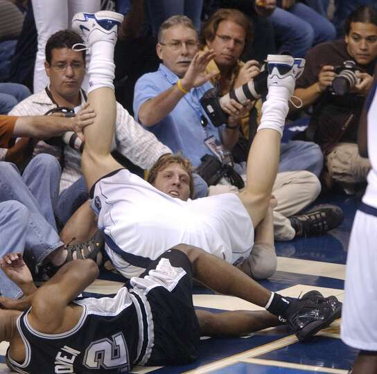 The Spurs' Bruce Bowen and the Mavericks' Dirk Nowitzki fall into courtside photographers during Gam